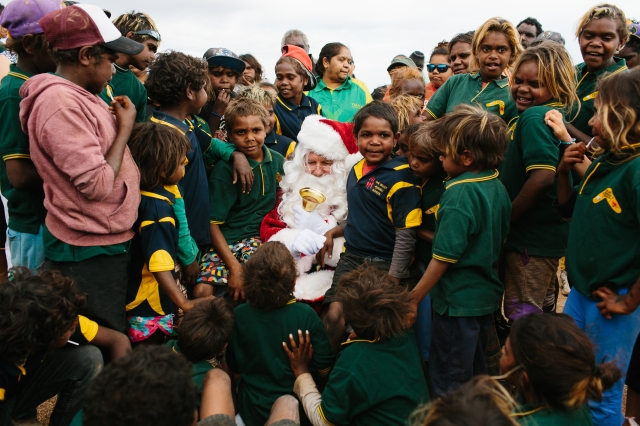 Santa seated in the desert surrounded by eager kids. Image Cameron Zegers Photography.